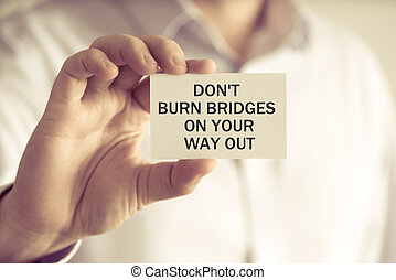 Businessman holding DONT BURN BRIDGES ON YOUR WAY OUT ...