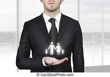 businessman holding family symbol in hand - businessman in...