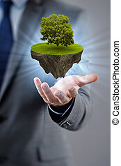 Businessman holding floating island with tree
