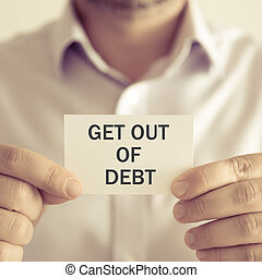 Businessman holding GET OUT OF DEBT message card