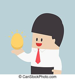 Businessman holding golden egg in his hand