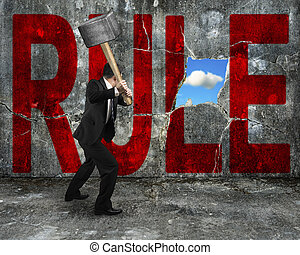 businessman holding hammer hitting red RULE word on concrete wall with nature sky cloud view through big hole