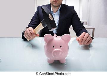 Businessman Holding Hammer Over Piggybank
