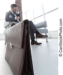 businessman holding his briefcase in office