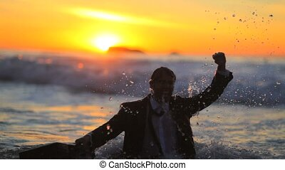Businessman holding his briefcase in the water during the...