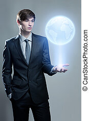 Businessman holding hologram of the earth