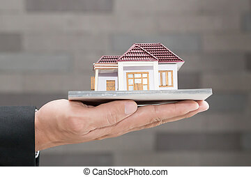 Businessman holding home model. Loan and real estate concept