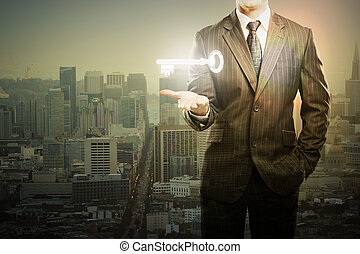 Businessman holding key in city