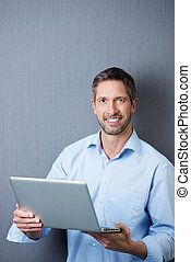 Businessman Holding Laptop Against Blue Wall