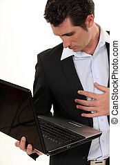 businessman holding laptop in one hand