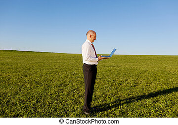 Businessman Holding Laptop On Grassy Field Against Sky