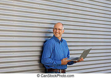 Businessman Holding Laptop While Looking Away Against Shutter