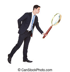 Businessman Holding Large Magnifying Glass