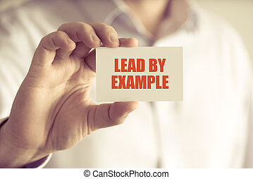 Businessman holding LEAD BY EXAMPLE message card