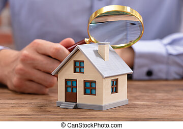 Businessman Holding Magnifying Glass Over House Model