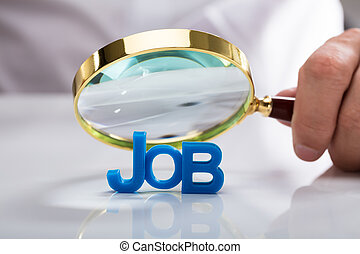 Businessman holding magnifying glass over job word