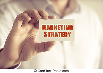 Businessman holding MARKETING STRATEGY message card