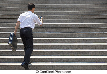 businessman holding mobile and in hurry to run up on stairs
