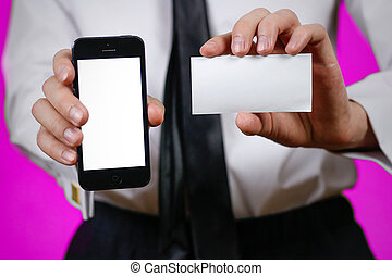 Businessman holding mobile phone and a business card (visit card) with text contact us. Close up. Isolated background.