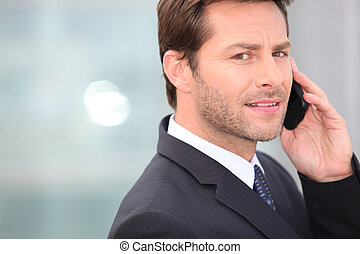 Businessman holding mobile telephone serious expression