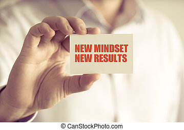 Businessman holding NEW MINDSET NEW RESULTS message card