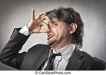 bad smell - businessman holding nose because of bad smell