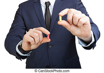 Businessman holding one pill in eatch hand on a white background
