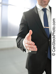 businessman holding out his hand for a handshake