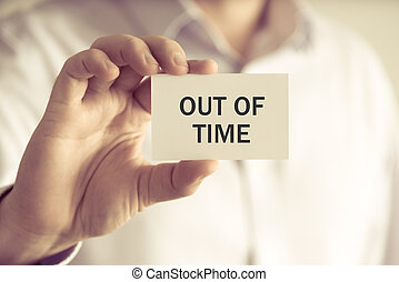 Businessman holding OUT OF TIME message card