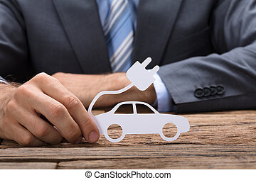 Businessman Holding Paper Electric Car At Table