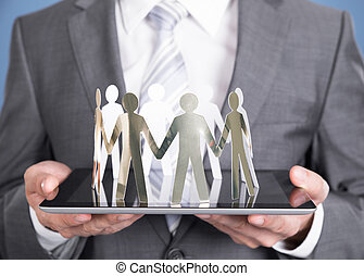 Businessman holding paper people on tablet