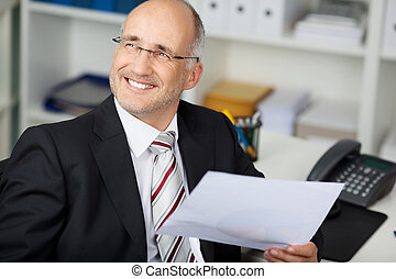 Businessman Holding Paper While Looking Away At Desk