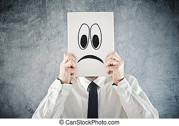 Businessman holding paper with sad face in front of his head. Unhappy businessman, office situation.
