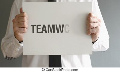 Businessman holding paper with Teamwork title. Business concept.