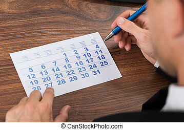 Businessman Holding Pen Looking At Calendar