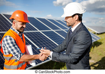 Businessman holding photovoltaic detail and shaking hand to a foreman.