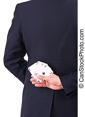 Businessman holding playing cards behind his back.