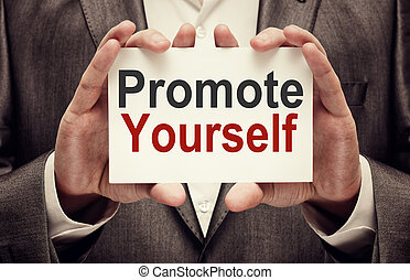 Businessman holding Promote yourself card in his hands