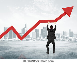 Businessman holding red arrow from business graph at city...