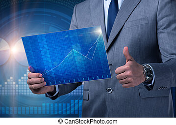 Businessman holding screen with market quotes