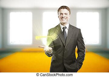 Businessman holding shining key