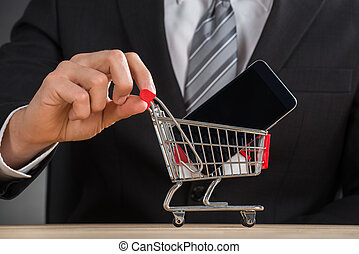 Businessman Holding Shopping Trolley With Mobile Phone