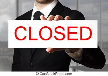 businessman holding sign closed - businessman in black suit...