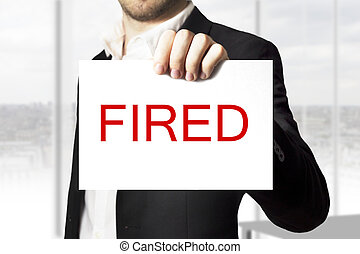 businessman holding sign fired
