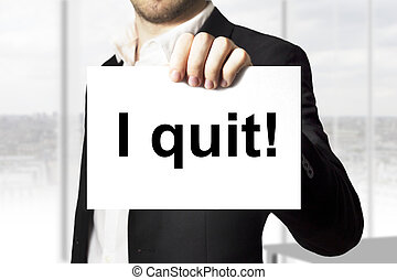 businessman holding sign i quit - businessman in office...