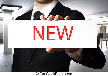 businessman holding sign new