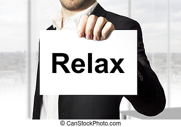 businessman holding sign relax - businessman in black suit...