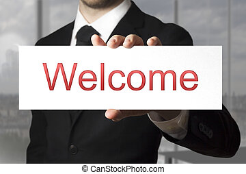 businessman holding sign welcome
