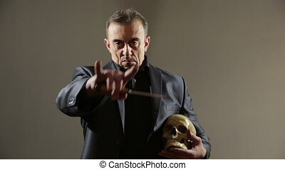 Businessman holding skull. gray background - Businessman...