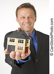 Businessman Holding Small House
